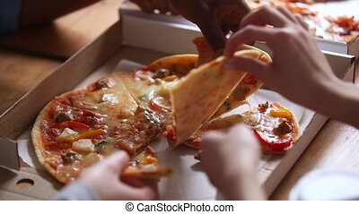 Hands of multiracial people grab italian pizza slices from...