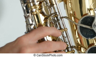 Hands of musician playing on saxophone close up