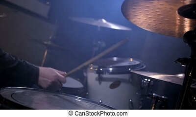 Hands of musician with drumsticks playing drums