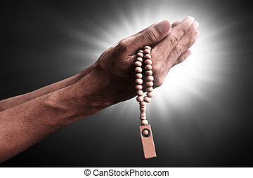 Hands of muslim man praying with rosary beads