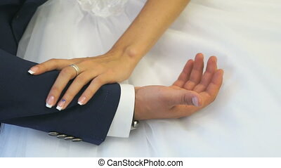 Hands of newlyweds on the wedding