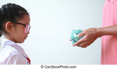 Hands of old woman grandmother giving clear piggy bank to Asian little girl over white background metaphor saving money for education concept