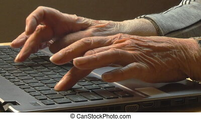 Hands of old woman typing on a laptop keyboard
