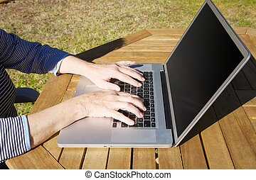 hands of old woman typing on laptop