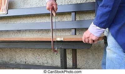 hands of older man working cutting plank with wood handsaw outside on the ground on picnic