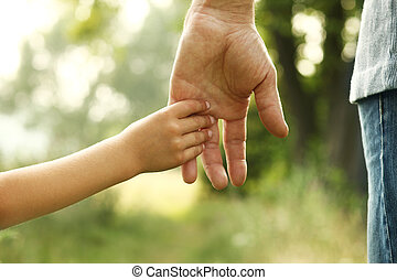 hands of parent and child in nature