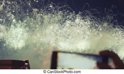 Hands of peoples taking photo of fireworks on smartphone. Close-up. Slow motion