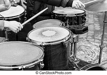 hands of performing musicians playing drum set in street