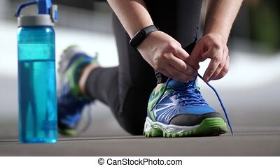 Hands of plus size woman runner tying shoelaces - Close-up...