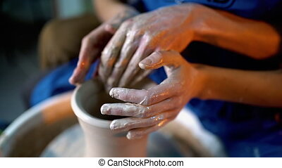 Hands of potter and his female student. Man and woman...