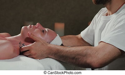 Hands of professional masseuse massaging woman's face in...