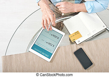 Hands of retired man with digital tablet and bank card checking balance online