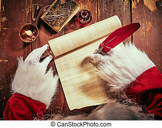 Hands of Santa Claus writing on a vintage scroll