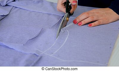 Hands of seamstress cutting fabric with scissors