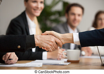 Hands of senior and young businessmen shaking at group meeting