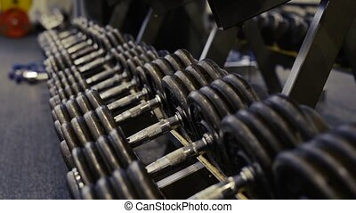 Hands of senior couple in gym working out with weights -...