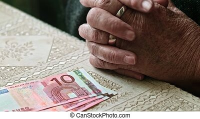 Hands of senior woman on table with some euro banknotes on