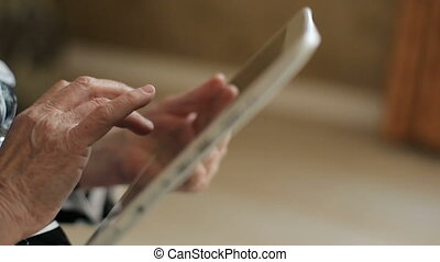 Hands of Senior Woman Uses Tablet PC