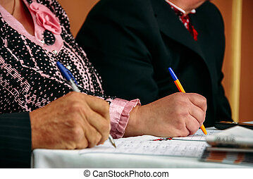 Hands of seniors with pens