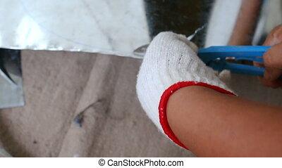 Hands of technician using hard scissor to cutting a sheet of...