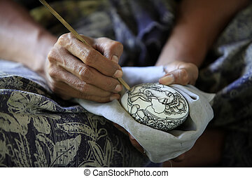 Hands of the artist drawing on an egg