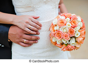 hands of the bride and groom with rings on a background of a wedding bouquet