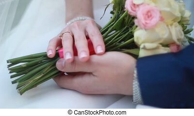 hands of the bride and groom with rings on a beautiful wedding bouquet