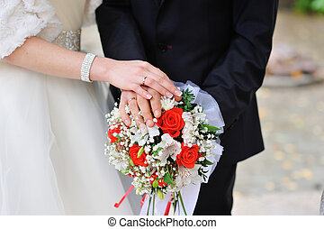 hands of the bride and groom with rings on a bouquet