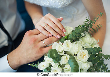 Hands of the bride and groom with rings on a wedding bouquet