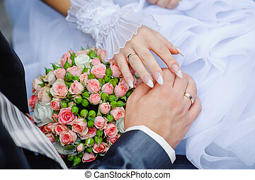 hands of the bride and groom with wedding rings on a background of the bouquet
