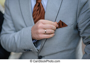 hands of the bride in a suit with a brown decor