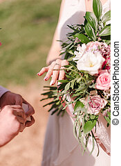 hands of the bride on the background of a wedding bouquet