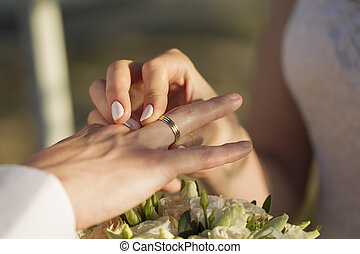 Hands of the bride put a ring to the groom. Wedding day.
