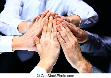 Hands of the business people forming a pyramid in the air.