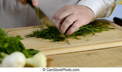 Hands of the cook knife big kitchen a fresh green fennel on...
