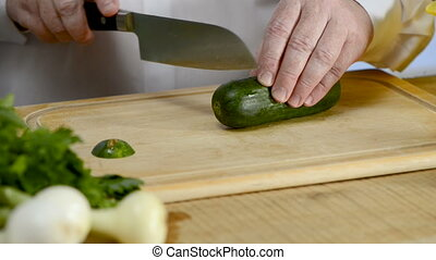 Hands of the cook knife big kitchen a fresh green cucumber on a chopping board from a tree
