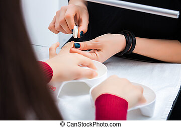 Hands of the girl in the baths with water during a manicure, cleansing the cuticle