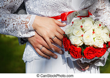 Hands of the groom and the bride with wedding rings and a bouquet from beige roses