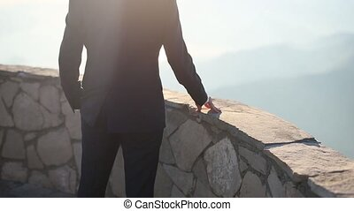 Hands of the groom on a stone border