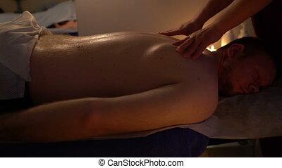 Hands of the masseur massages your back men