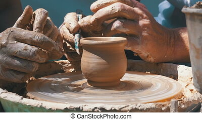 Hands of the Master Potter and Vase of Clay on the Potter's Wheel close-up. Master crock man. Twisted potter's wheel. Man creates a work of art. Master kneads the clay.