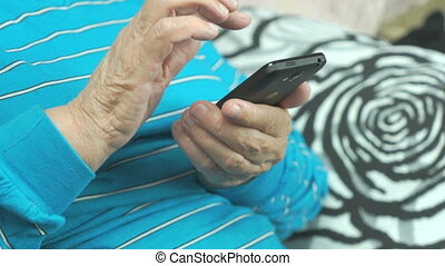 Hands Of The Old Woman And Smartphone