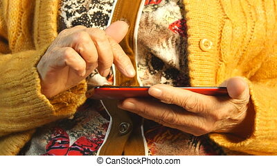 Hands of the old woman and smartphone. Close up