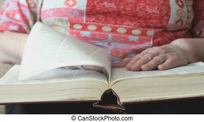 Hands of the old woman holding a book