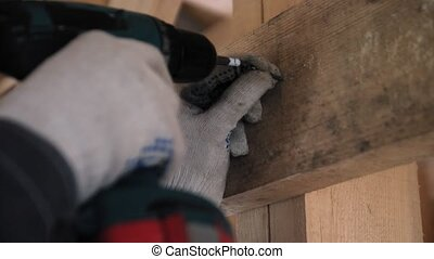 Hands of the person in working gloves twist the self-tapping screw in a wooden board. Screwing the screw in a wooden board. Frame building. Close up. 4k