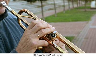 Hands of the trumpeter who plays his musical instrument in the park.