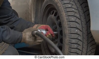 Hands of the worker twisting bolts on car wheel.
