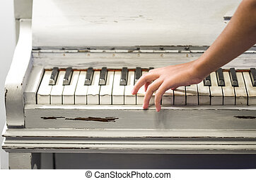 hands of the young musician play an old piano
