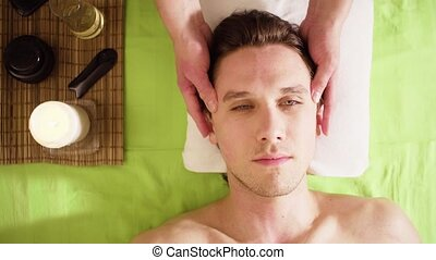Hands of therapist doing massage of male face