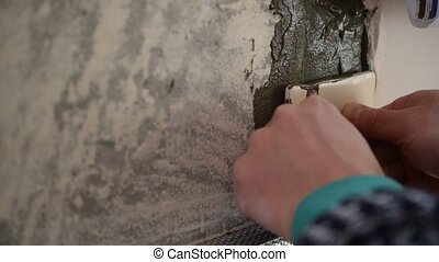Hands of tile worker gluing square tiles to a wall - Hands...